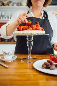 Baker in apron decorating cake